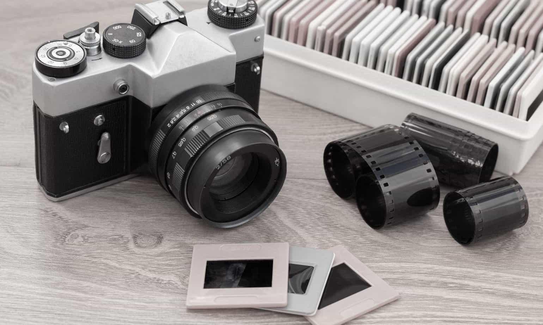 Vintage camera, slides and negatives on wooden table